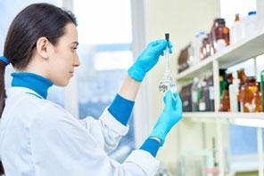 Frau im Labor trägt Gumihandschuhe zum Schutz vor Chemikalien