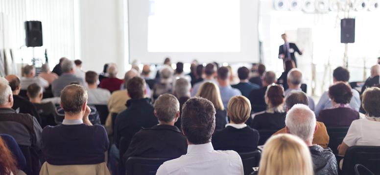 Viele Menschen sitzen in einer Konferenz