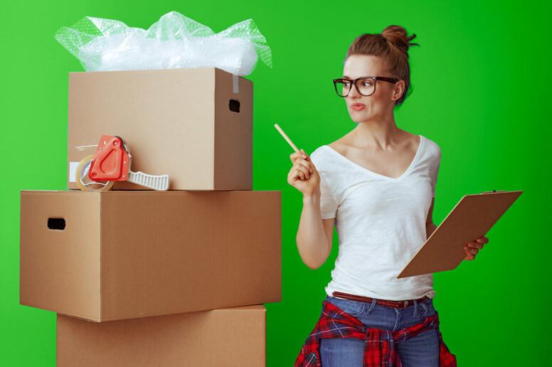 Eine Frau mit Brille und Klemmbrett guckt auf einen Stapel Umzugskartons