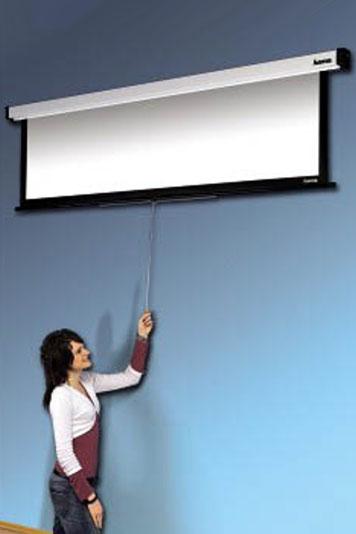Frau zieht, die an einer Wand befestigten, Rolloleinwand für Präsentation herunter