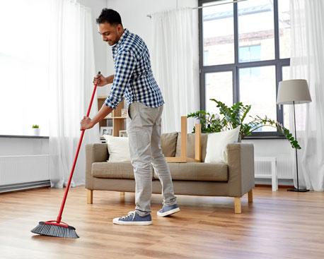 Mann fegt den Boden eines Wohnzimmers