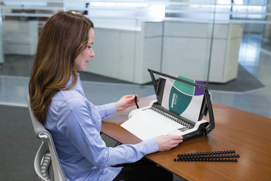 Frau bindet ein Dokument mit einem Bindegerät