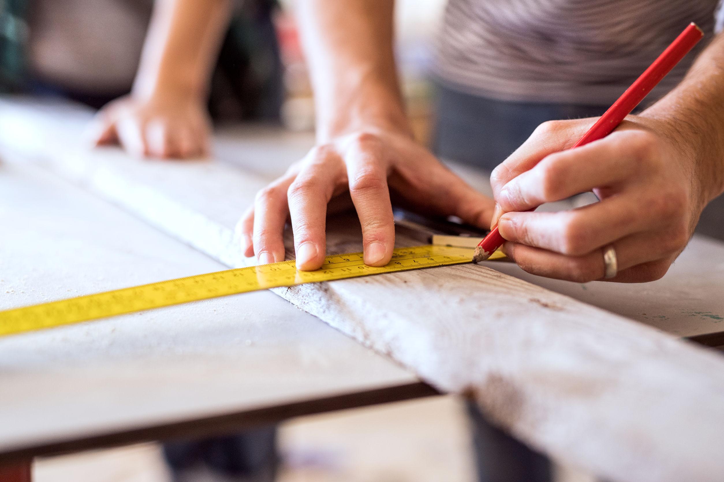 Hand markiert mit Hilfe eines Bleistifts eine Beschnittkante bei einem Holzbrett