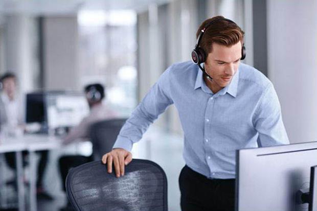 Mann im Büro telefoniert mit Bluetooth-Headset
