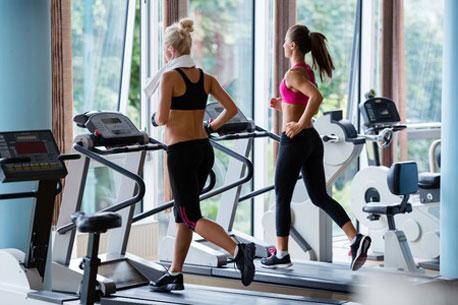Zwei Frauen laufen auf Laufbändern in einem Fitnessstudio