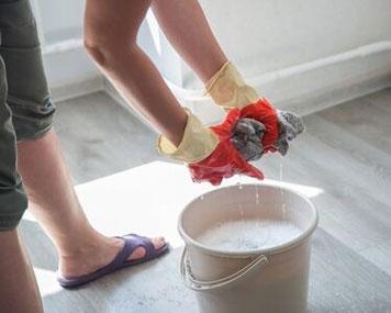 Auswringen eines Bodentuches über einem Eimer