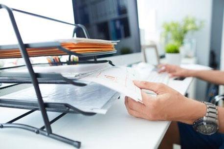 Person zieht Unterlagen aus einer Briefablage