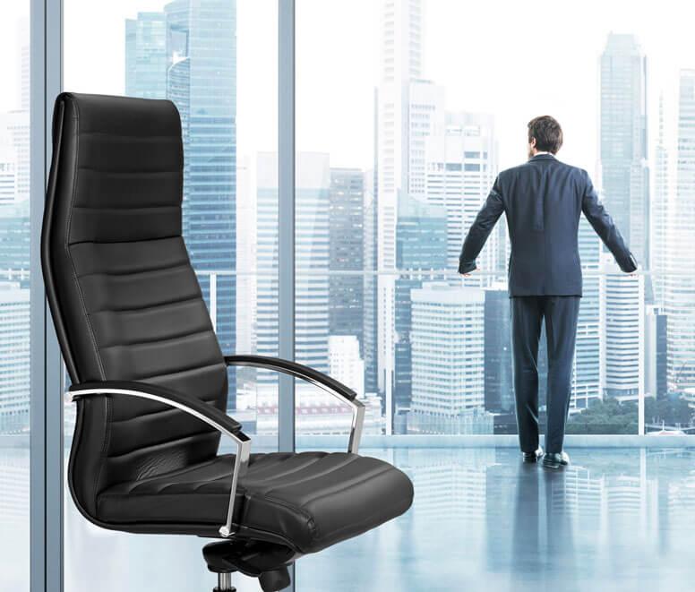 Chef genießt Aussicht aus Bürokomplex während im Vordergrund ein Chefsessel steht