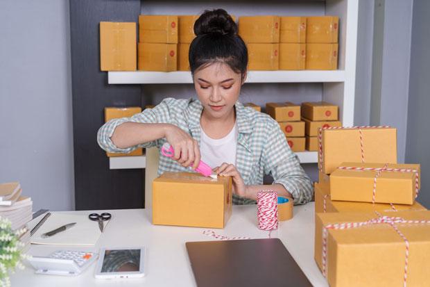 Frau öffnet Paket mit einem rosafarbenen Cutter