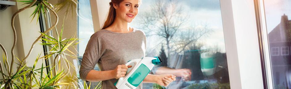 Attraktive Frau mit einem Fenstersauger vor suaberen Fenstern