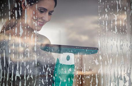 Junge Frau reinigt mit einem Nasssauger ihre Fenster