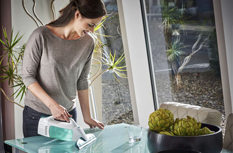 Junge Frau reinigt mit einem Trockensauger einen Glastisch
