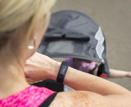 Junge, Blonde Frau überwacht mit einem Fitnesstracker ihr Training