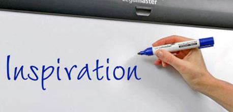 Jemand schreibt mit einem Flipchartmarker das Wort Inspiration an einen Flipchart