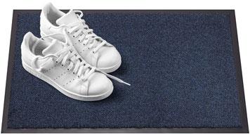 Fußmatte mit weißen Turnschuhen darauf