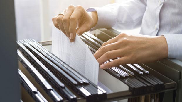 Frau sortiert Unterlagen in einem Hängeregistraturschrank