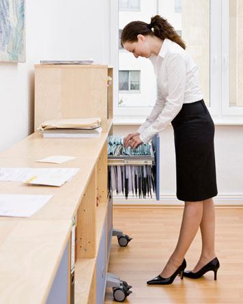 Frau an einem Hängeregistraturschrank einer Kanzlei