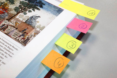 verschiedenfarbige Haftmarker als Seiten-Markierung in einem Buch