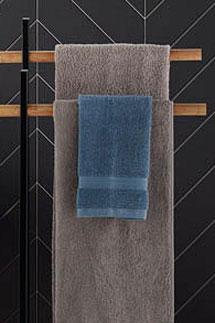 Blaues Gästetuch hängt vor einem grauen Handtuch an einem Handtuchständer