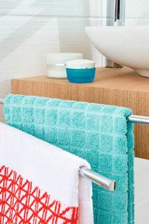 Farbenfrohe Handtücher hängen neben einem Waschbecken