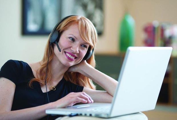 Frau unterhällt sich über Videokonferenz per Headset und Laptop