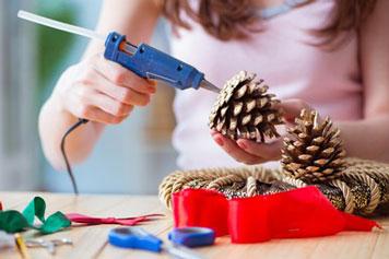 Junge Frau klebt mit einer Heißklebepistole einen Fichtenzapfen auf einen Kranz