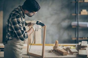 Mann klebt in der Hobbywerkstatt einen Bilderrahmen mit Heißkleber