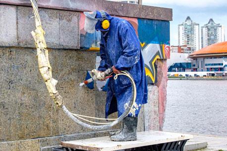 Arbeiter entfernt ein Graffiti mit einem Hochdruckreiniger