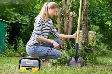 Frau säubert einen Spaten im Garten mit einem Akku-Hochdruckreiniger von KÄRCHER