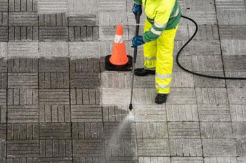 Straßenarbeiter reinigt Platten mit einem Benzin-Hochdruckreiniger