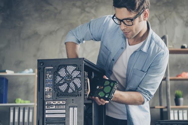 Mann baut eine Festplatte in einen Computer ein