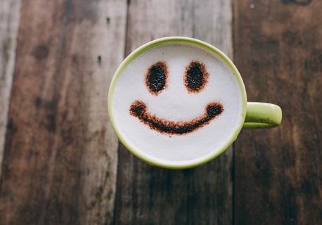 Ein glückliches Gesicht auf einer Kaffeetasse