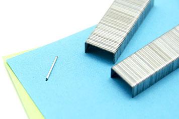Eine Heftklammer hält farbiges Papier zusammen während zwei Heftklammern-Blöcke darüber liegen