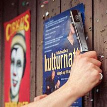 Aufhängen eines Plakates an einer Bretterwand mit Hilfe eines Schlagtackers