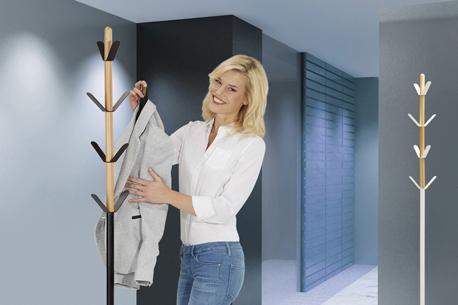 Frau hängt ihren Blazer an einer schwarzen Stand-Garderobe ab