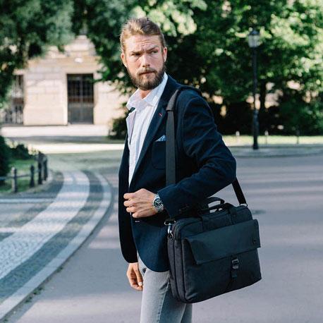 Mann läuft über eine Straße und trägt eine Laptoptasche über der Schulter