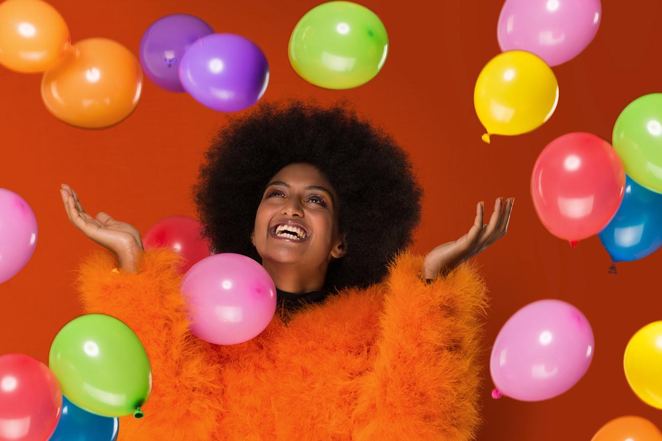 Junge Frau in kannligem, orangenem Pullover erfreut sich an einer Vielzahl kleiner Ballons