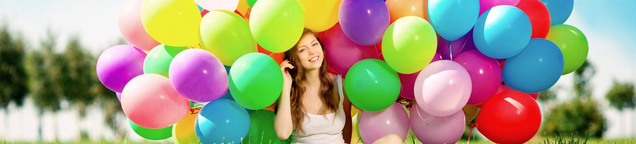 Junge Frau sitzt in Mitten einer großen Traube bunter Ballons