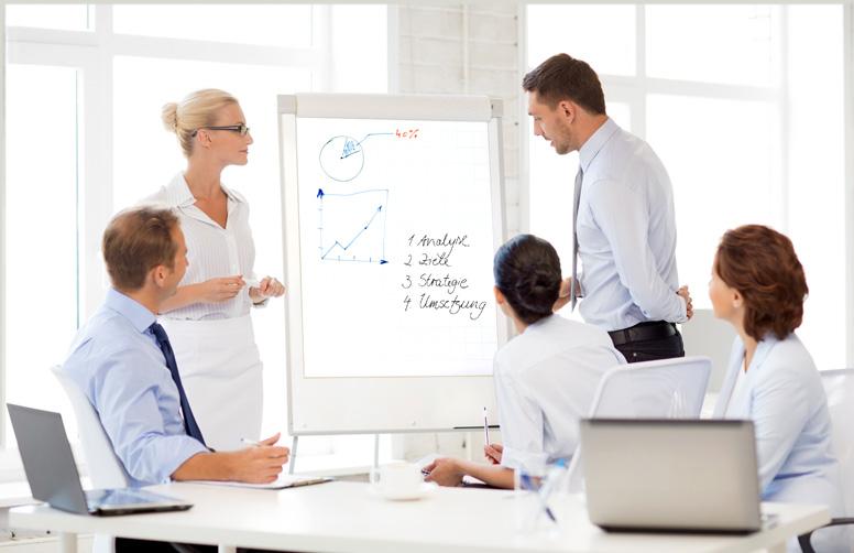 Eine Arbeitsgruppe arbeitet gemeinsam an einer Moderationswand
