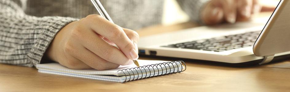 Junge Frau schreibt in ein kleines Notizbuch