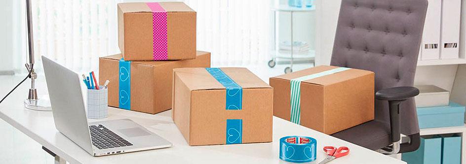Bunte Packbänder an Kartons auf einem Schreibtisch