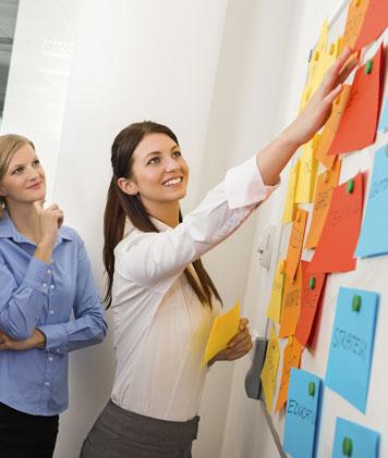 Frau zeigt auf Zettel an einer Pinnwand