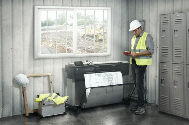 Bauleiter druckt sich einen Plan auf einem HP Plotter in einem Baustellen-Container aus