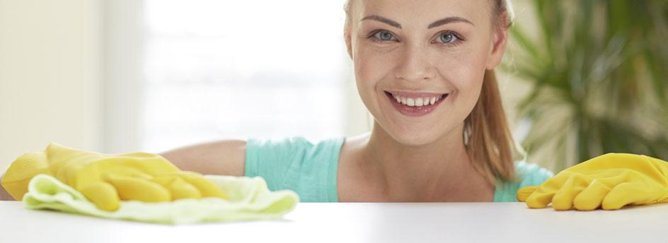 Frau putzt lächelnd eine weiße Oberfläche