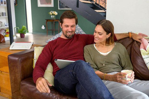 Paar surft auf Sofa im Internet mit einem W-LAN-Router