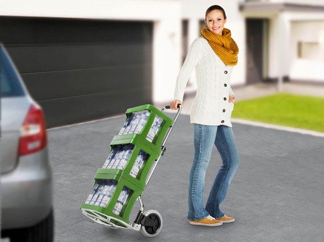 Frau transportiert 3 Kisten Sprudel mit einer Sackkarre vom Auto ins Haus
