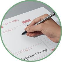 Detailabbildung von einer Hand, die etwas auf einer Schreibtischunterlage notiert