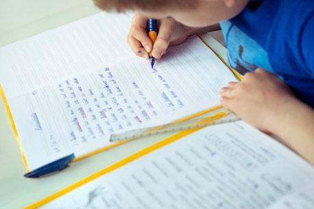 Junge schreibt in ein Schulheft für die 3. Klasse