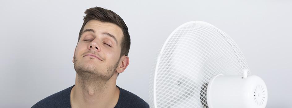 Ein Mann genießt eine kühle Brise vor einem Standventilator