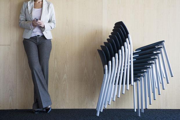 Frau steht neben einem Stapel Stühle